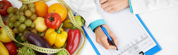 Fruits and vegetables and a flexible measuring tape on a table beside a clipboard